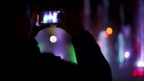 Kolorowa dancingowa fontanna przy nocą Zwolnionego tempa zbliżenia materiał filmowy strumienie woda na ciemnym tle _ zdjęcie wideo