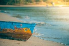 Kolorowa drewniana łódź rybacka na piasek plaży z morze fala w tle w rocznika stylu Obraz Stock