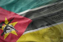 Kolorowa falowanie flaga państowowa Mozambique na amerykańskim dolarowym pieniądze tle Obrazy Stock