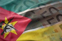 Kolorowa falowanie flaga państowowa Mozambique na euro pieniądze banknotów tle Zdjęcia Stock
