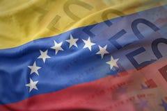 Kolorowa falowanie flaga państowowa Venezuela na euro pieniądze banknotów tle Obraz Stock