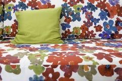 Kolorowa graficzna kwiatu druku tkaniny kanapa z zieloną jedwabniczą poduszką Fotografia Royalty Free