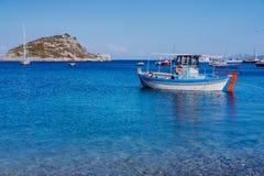 Kolorowa grecka Śródziemnomorska łódź rybacka przy spokojną jasną błękitną wody morskiej zatoką na wczesne lato ranku Biel skała  obrazy royalty free