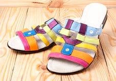 Kolorowa kobieta heeled sandały na lekkim drewnianym tle Fotografia Stock