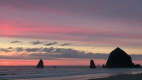 Kolorowa nieba i haystack skała przy działem wyrzucać na brzeg w Oregon zbiory wideo