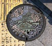 """Kolorowa Osaka manhole pokrywa na świetle słonecznym Japoński język znaczy """"The North† obrazy stock"""