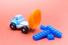Kolorowa zabawki ciężarówka na różowym tle z konstruktorów blokami i zdjęcia stock