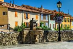 Kolorowe średniowieczne fasady z wodną fontanną w Moustiers-Sainte-Marie zdjęcie stock