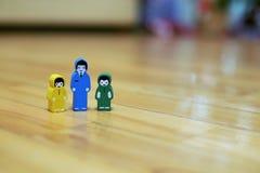 Kolorowe drewniane postacie córka z synem i ojciec na tle drewniany podłogowy zakończenie obrazy royalty free