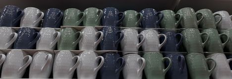 Kolorowe filiżanki na półce w sklepie Obraz Royalty Free