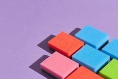 Kolorowe gąbki odizolowywać na błękitnym tle zdjęcia stock