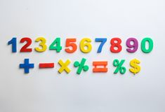 Kolorowe magnesowe liczby i matematyka symbole na białym tle obrazy stock