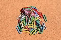 Kolorowe papierowe klamerki odizolowywać na korkowym tle Fotografia Royalty Free