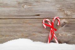Kolorowe pasiaste czerwieni i białych Xmas cukierku trzciny z zima śniegiem Fotografia Stock