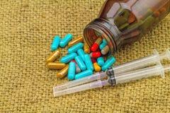 Kolorowe pigułki, butelek pastylki, strzykawki i igielny kłamstwo posypujący, Obrazy Stock