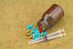 Kolorowe pigułki, butelek pastylki, strzykawki i igielny kłamstwo posypujący, Zdjęcie Stock