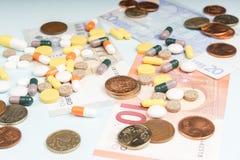 Kolorowe pigułki na tle różnorodni Euro banknoty i monety zdjęcie stock