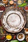 Kolorowe pikantność i ziele wokoło pustego rocznika talerza na nieociosanym drewnianym tle, odgórny widok fotografia royalty free