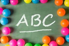 Kolorowe plastikowe piłki na zielonym ABC przy ce i chalkboard Fotografia Royalty Free