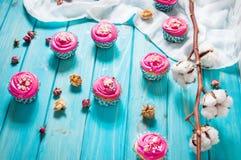 Kolorowe różowe babeczki na błękitnym drewnianym tle Fotografia Stock