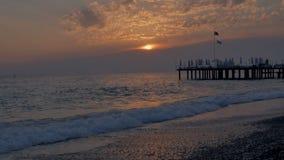 kolorowe słońca Denny widok z, molo, otoczak, i wyrzucać na brzeg Czasu upływ zbiory wideo