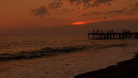 kolorowe słońca Denny widok z, molo, otoczak, i wyrzucać na brzeg Czasu upływ zbiory