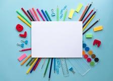 Kolorowe szkolne dostawy nad papierem na błękitnym tle z miejscem dla twój teksta obrazy royalty free