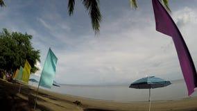 Kolorowe sztandar flaga i Parasolowy Parasol wykładają na tropikalnej pustej piaskowatej plaży zbiory wideo