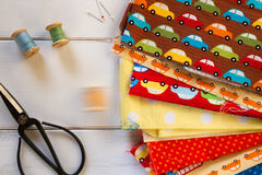 Kolorowe tkaniny z roczników nożycami, szpilkami, pomiarową taśmą i tocznymi bawełnianymi niciami na białym drewnianym stole, Obraz Stock