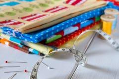 Kolorowe tkaniny z szpilkami, pomiarową taśmą i tocznymi bawełnianymi niciami, Zdjęcie Royalty Free