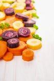 Kolorowe tnące marchewki na białym drewnianym tle Obrazy Stock