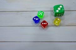 Kolorowego akrylowego kostka do gry kostka do gry światła wieśniaka drewniana powierzchnia Zdjęcie Royalty Free