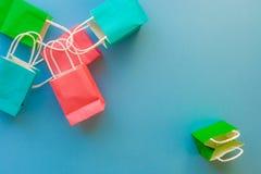 Kolorowego zakupy papierowe torby na błękitnym tle z odbitkowym space/ Obrazy Royalty Free
