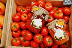 Kolorowi błyszczący świezi warzywa Pomidory z konserwuje hommemade i handmade pomidorowym sokiem na półce supermarket lub obraz stock