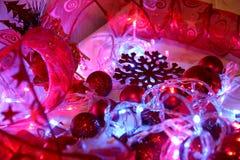 Kolorowi boże narodzenia i nowego roku tło dekorują z światłami girlandy, iskrzaste czerwone piłki, płatek śniegu i dekoracyjny, zdjęcie stock