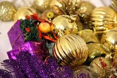 Kolorowi boże narodzenia i nowego roku tło dekorują z błyskotliwymi złocistymi piłkami i lilym koloru kwadrata prezentem, lily pt zdjęcie stock