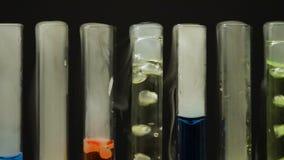 Kolorowi ciecze gotuje się w próbnych tubkach, nielegalny narkotyk produkcja, laboratorium zdjęcie wideo