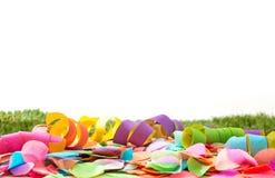 Kolorowi confetti i streamers na trawie przed tłem Obrazy Stock