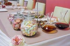Kolorowi cukierki w słojach na stole Zdjęcia Stock