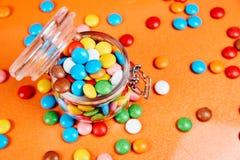 Kolorowi cukierki w szklanym słoju na czerwonym pomarańcze tle obraz stock