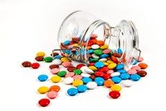 Kolorowi cukierki w szklanym słoju rozpraszali odosobnionego na bielu zdjęcie royalty free