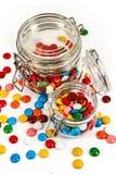 Kolorowi cukierki w szklanym słoju rozpraszali odosobnionego na bielu obrazy stock