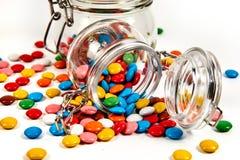 Kolorowi cukierki w szklanym słoju rozpraszali odosobnionego na bielu obrazy royalty free
