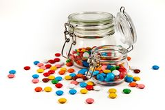 Kolorowi cukierki w szklanym słoju rozpraszali odosobnionego na bielu fotografia stock