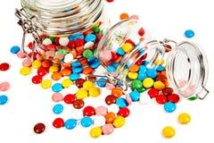 Kolorowi cukierki w szklanym słoju rozpraszali odosobnionego na bielu zdjęcia royalty free