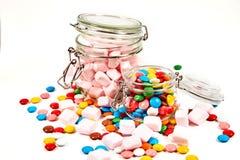 Kolorowi cukierki w szklanym słoju rozpraszali odosobnionego na bielu zdjęcie stock