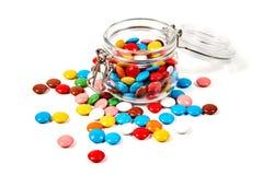Kolorowi cukierki w szklanym słoju rozpraszali odosobnionego na bielu obraz royalty free
