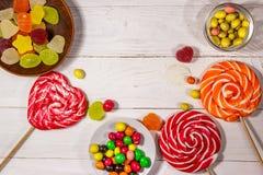 Kolorowi czekoladowi cukierki, lizaki i galareta cukierki na białym drewnianym stole, zdjęcie royalty free