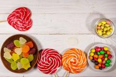 Kolorowi czekoladowi cukierki, lizaki i galareta cukierki na białym drewnianym stole, fotografia stock