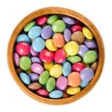 Kolorowi czekoladowi cukierki w drewnianym pucharze nad bielem Fotografia Stock
